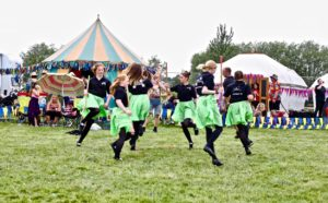 Kids area at a festival with a dance troupe